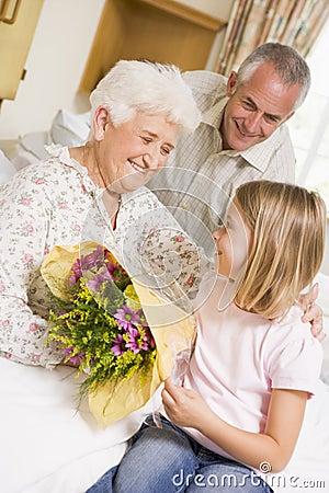 Enkelin, die ihrer Großmutter Blumen gibt