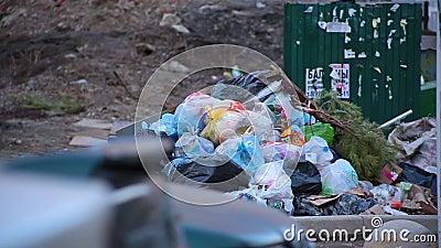 Enorm förrådsplats för närbild av avskrädepåsar med avfalls som ligger på jordning bredvid soptunnor i bostads- gård stock video