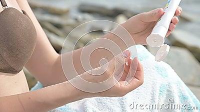 Enschließende weibliche junge Hände an der Meeresküste, die den Sonnenschutz aus einer Röhre presst Die Pflegekonzepte stock video