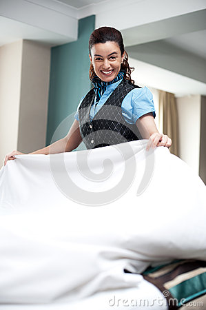 Enthusiastic female attendant arranging bed sheet
