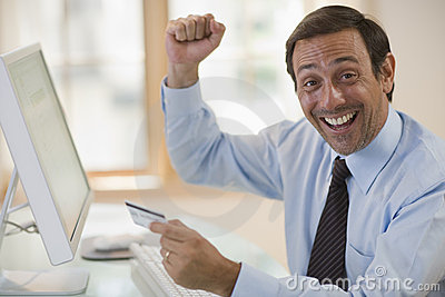 Enthusiastic man using credit card and computer
