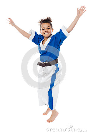 Enthusiastic young girl kid in karate uniform
