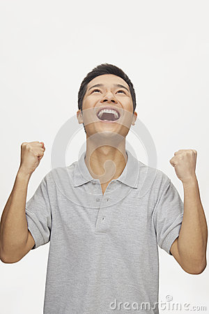 Enthusiastic young man with arms raised and looking up, studio shot