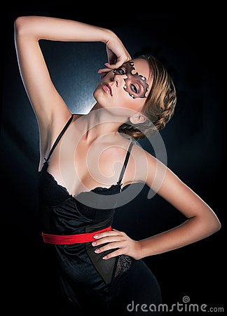 Enticing lovely masked girl standing in studio