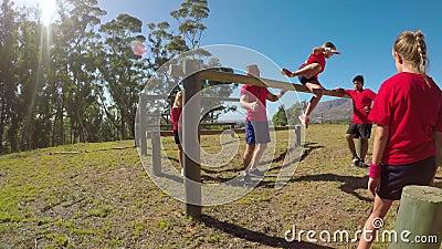Entraîneur aidant une fille d'école dans la traînée de forme physique pendant le parcours du combattant 4k clips vidéos