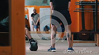 Entrenamiento deportivo - un atlético con piernas tatuadas en cuclillas con un peso en las manos almacen de metraje de vídeo