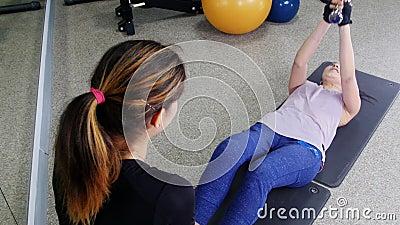 Entrenamiento Una mujer joven que bombea su ABS con el instructor que lleva a cabo una pesa de gimnasia almacen de video