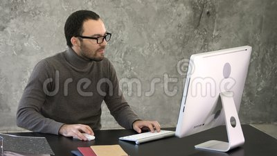 Entrepreneur angry and furious at computer. Reaction to something on the screen of the monitor. Professional shot in 4K resolution. 007. You can use it e.g. in stock video footage