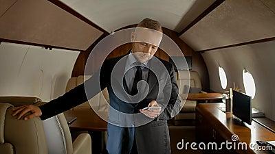 Entrepreneur attirant avec smartphone à l'intérieur d'un jet privé banque de vidéos