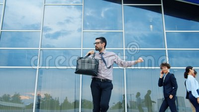 Entrepreneur joyeux avec une mallette dansant à l'extérieur en s'amusant avec succès banque de vidéos
