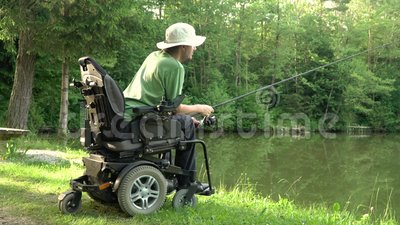 Entschließung 4k des glücklichen Mannes in einem elektrischen Rollstuhl, der in dem schönen Teich im natue an einem sonnigen Tag