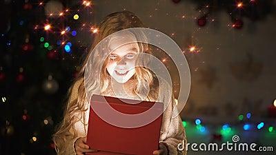 Entzückende blonde Mädchenöffnungsgeschenkbox, magische Weihnachtsatmosphäre, glühender Effekt stock video footage
