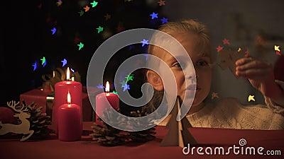 Entzückendes Mädchen, das mit hölzernem Engel, funkelnder Weihnachtsbaum, Fantasie spielt stock video