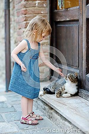 Entzückendes glückliches kleines Mädchen und eine Katze