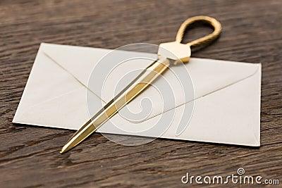 Envelope and brass letter opener on a desk