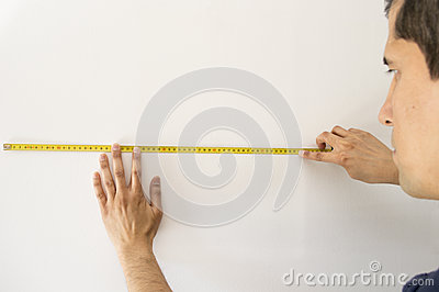 Eople pointing at a measuring tape on the wall