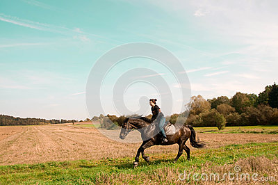 Equestrienne rides on the hillside.