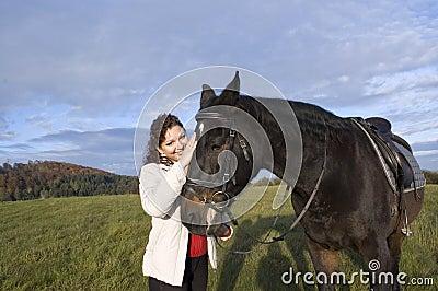 Equestrienne  strokes a horse.