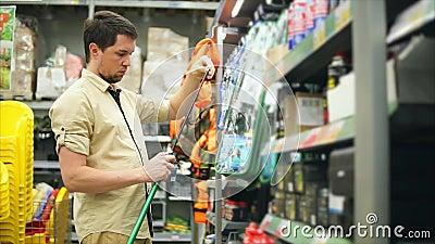 Equipaggi il cliente che sceglie le canne da pesca nel deposito per pescare Lui che prende barretta stock footage