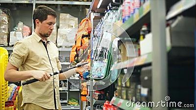 Equipaggi il cliente che sceglie le canne da pesca nel deposito per pescare Lui che prende barretta archivi video
