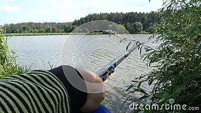 Equipaggi la canna da pesca e la pesca della tenuta della mano del ` s Chiuda su in 4K stock footage