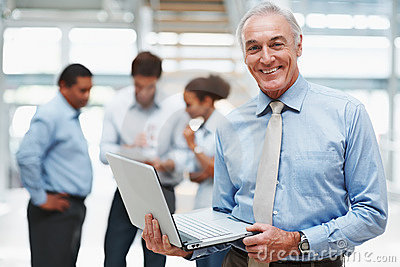 Equipaggi per mezzo di un computer portatile con i colleghi alla parte posteriore