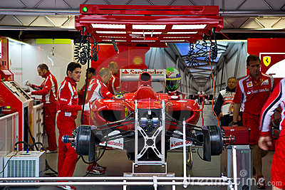 Equipe de Ferrari que prepara o carro de Felipe Massaâs Fotografia Editorial