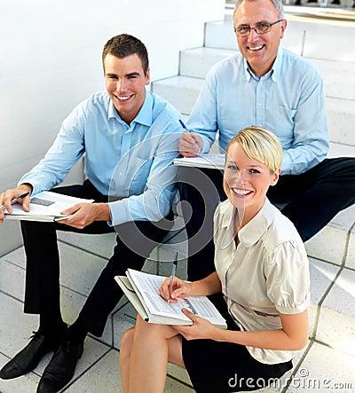 Equipe feliz do negócio que senta e que compara notas