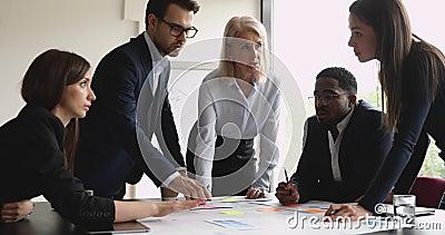 Equipe multiracial séria com empresárias brainstorming na papelada