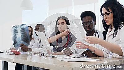 Equipo de doctores jovenes multiétnicos que tienen una reunión en la sala de conferencias en el hospital moderno Grupo de multiét almacen de metraje de vídeo