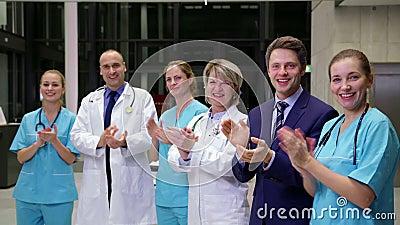 Equipo de doctores y de hombre de negocios que aplauden durante la reunión almacen de video