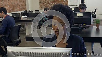 Equipo de escritorio de trabajo afroamericano de la mujer de negocios almacen de video
