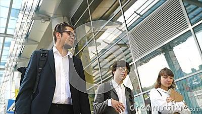 Equipo de negocios dos hombres y mujeres caminando juntos afuera almacen de metraje de vídeo