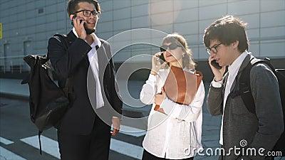 Equipo de negocios dos hombres y mujeres trabajando juntos fuera todos están llamando metrajes