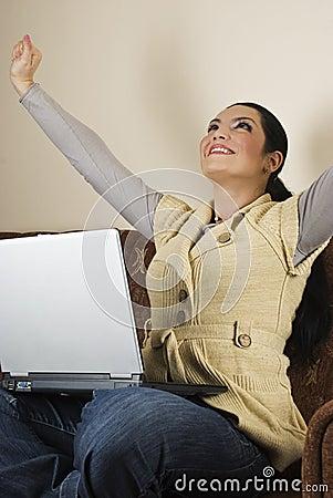 Erfolgreiche Frau, die Laptophaus verwendet
