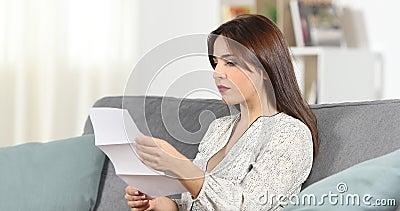 Ernste Frau, die zu Hause einen Brief liest