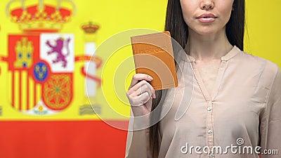 Ernsthafte Dame mit Reisepass, isoliert auf dem Hintergrund der spanischen Flagge, Wahl stock footage