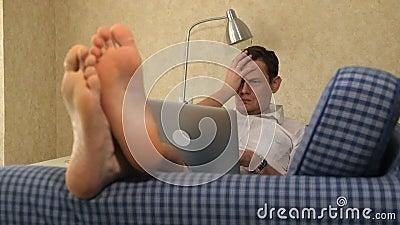 Ernstige bedrijfsmens die op de laag liggen, die met laptop, hartstocht werken voeten, close-up stock footage