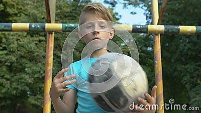 Ernstige jongen met een camera die op de bal lijkt, gezonde activiteit in de zomer, motivatie stock videobeelden