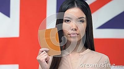 Ernstige vrouw met paspoort, vlag van Groot-Brittannië, zakenreis naar Engeland stock videobeelden