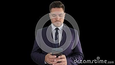 Ernstige zakenman die bericht op zijn telefoon sms't, alpha- kanaal stock videobeelden