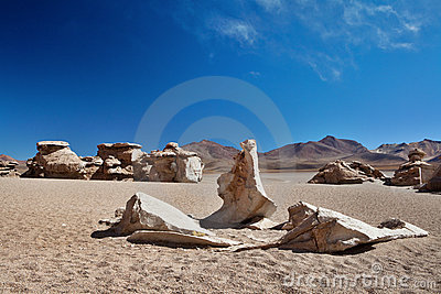 Eroded rocks laying in sand desert of Andes