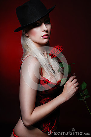 Erotic blonde with a red rose in hands