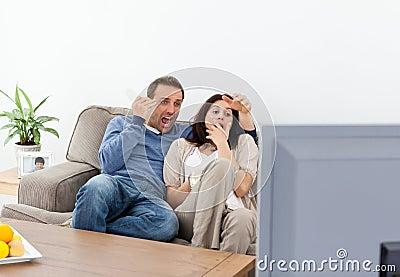 Erschrockene Paare, die einen Horrorfilm auf dem Fernsehapparat überwachen