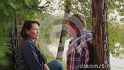 Erwachsener Ehepaar am Ufer des Flusses im Nadelwald Happy Mann und Frau entspannen sich an der Flussküste in Pinienwäldern stock video