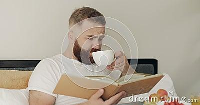 Erwachsener liest Geschichte und trinkt Kaffee, während er mit einem Tablett voller Nahrung auf den Beinen sitzt Schöner Bartmann stock video footage