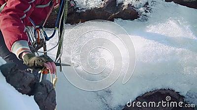 Escalador abajo de la grieta de la montaña, inclinándose en su mano y una selección de hielo Él tiene una mochila en sus hombros  almacen de video