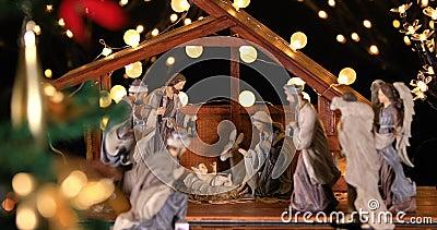 Escena de la Natividad de Jesucristo con luces atmosféricas cerca del árbol de Navidad metrajes