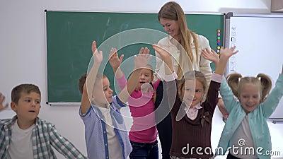 Escola primária, grupo de mãos de salto e de ondulação do divertimento das crianças próximo ao professor no fundo da placa