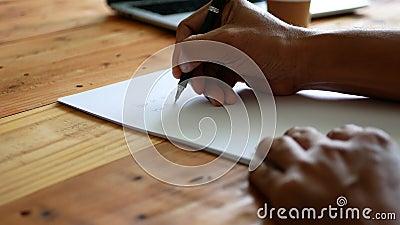 Escribiendo la mano de un hombre sobre un papel blanco en una mesa con una taza de café y un ordenador portátil cercano almacen de metraje de vídeo